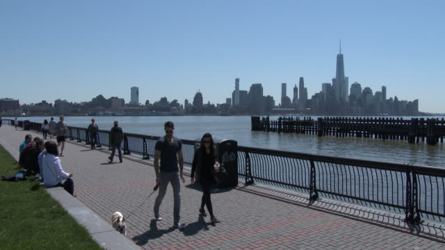 hipsters, people enjoying nice weather at pier a, hoboken nj / manhattan skyline - dog walker stock videos and b-roll footage