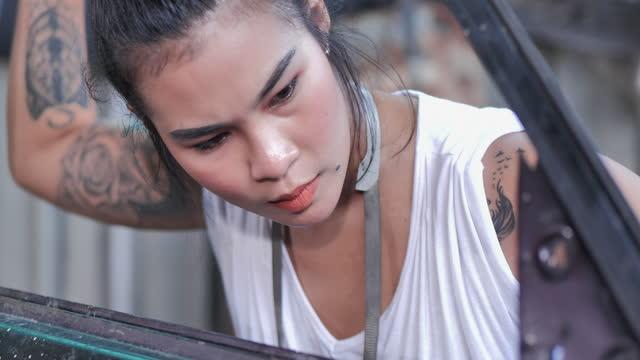 vídeos y material grabado en eventos de stock de hipter de mujeres jóvenes asiáticas de 27 añosold con tatuajes en los brazos que es mecánico reparando un coche en el taller de reparación de automóviles. concepto mujeres en trabajos de cuello azul. - carrocería