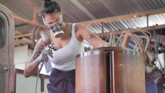 vidéos et rushes de hipterof jeunes femmes asiatiques ayant des tatouages sur les bras qu'elle peint avec pistolet de pulvérisation dans l'atelier. - femme de pouvoir