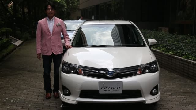"""""""hiroshi nakamura, project general manager of toyota motor corp., poses with the company's corolla fielder hybrid vehicle at its unveiling in tokyo,... - fielder stock videos & royalty-free footage"""