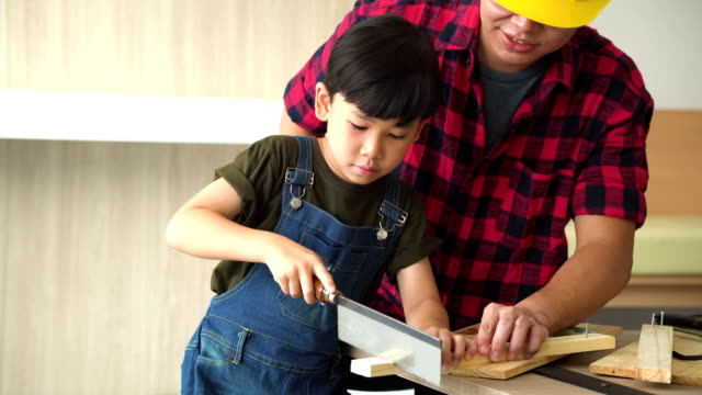 his son use saw with father while working on a piece of wood - repairman stock videos & royalty-free footage