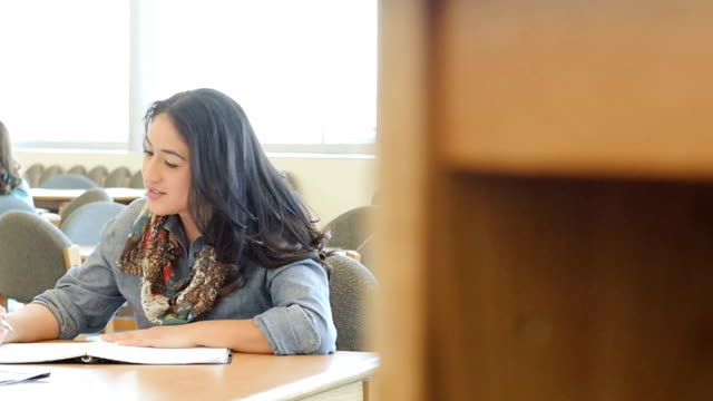 hispanic adult male and female students studying together at table in college library - community college stock videos & royalty-free footage