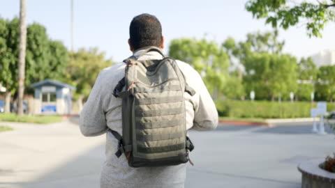 spansktalande amerikanska veteran college student walking på campus - kamouflage bildbanksvideor och videomaterial från bakom kulisserna