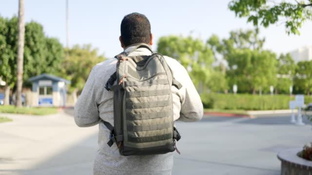 hispanic american veteran college student walking on campus - camouflage stock videos & royalty-free footage