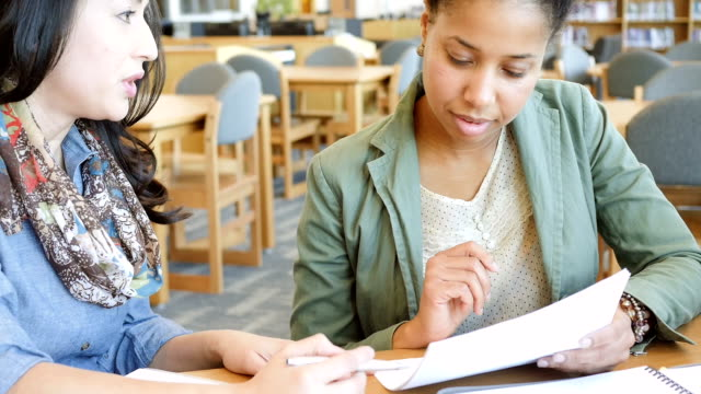 Hispanic and African American adult female college students studying together