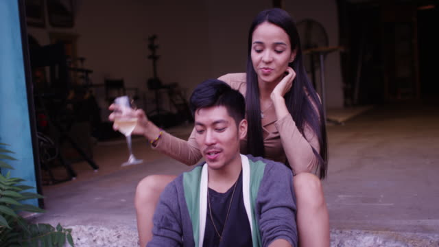 hispanic and asian cute young happy couple sitting in loading dock opening talking and drinking at party - プエルトリコ人点の映像素材/bロール