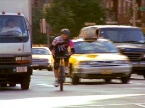 Hispanic bike messenger weaving thru traffic on city street / NYC