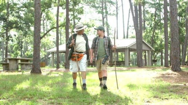 stockvideo's en b-roll-footage met hispanic jongen en grootvader wandelen in een park - 12 13 jaar
