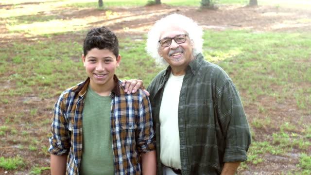 stockvideo's en b-roll-footage met spaanse jongen en grootvader staande in park - 12 13 jaar