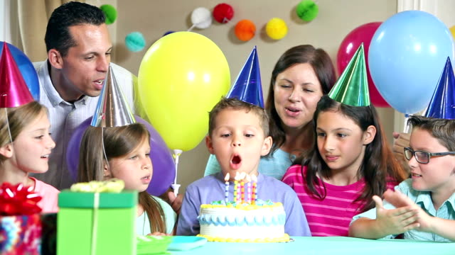 hispanic boy blows out candles on birthday cake - party hat video stock e b–roll