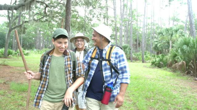 stockvideo's en b-roll-footage met spaanse jongen, vader en grootvader wandelen in een park - 12 13 jaar