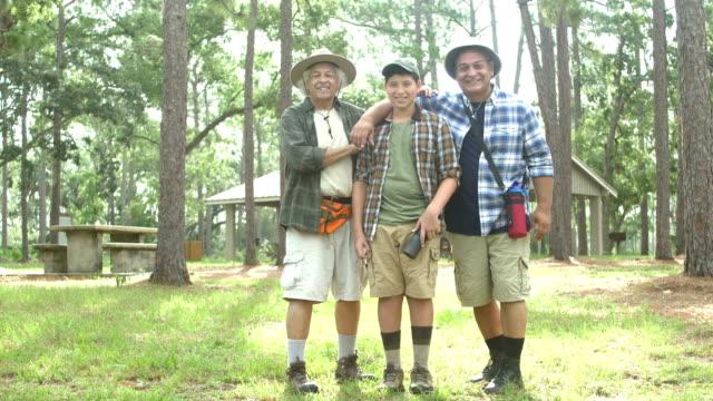 ヒスパニック系の少年、父と祖父が公園に立っている - 大家族点の映像素材/bロール