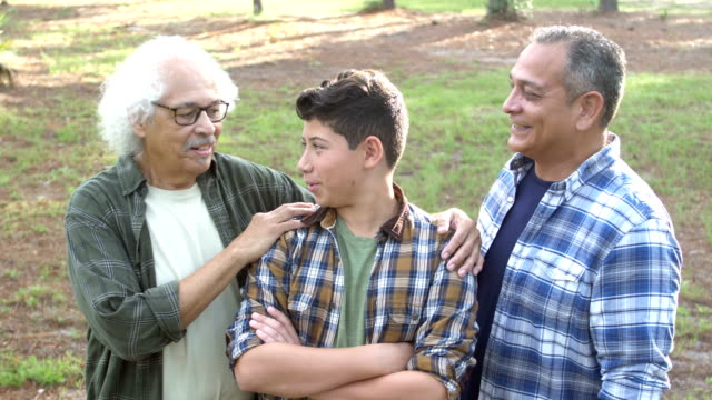 Hispanic boy, father and grandfather standing in park