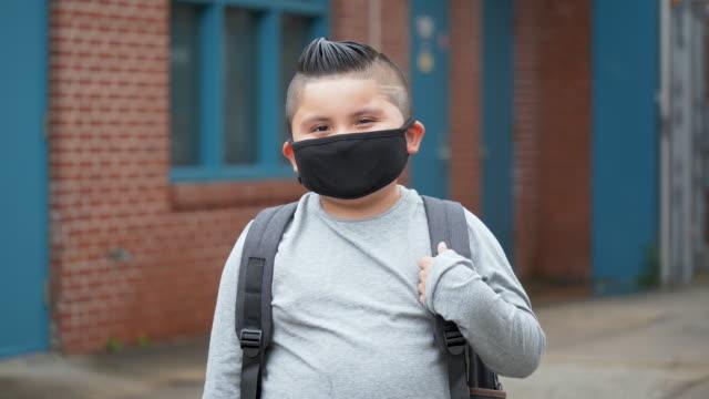 hispanic boy outside elementary school wearing face mask - elementary school building stock videos & royalty-free footage