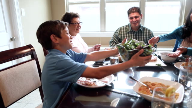 hispanic boy passing food around dinner table with multi-generational family - breakfast table stock videos and b-roll footage