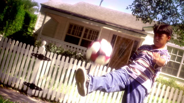 overexposed canted hispanic boy playing with soccer ball in front of house / florida - overexposed stock videos & royalty-free footage