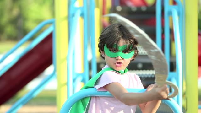 vídeos de stock, filmes e b-roll de garoto hispânico fingindo ser um super-herói - balanço equipamento de playground