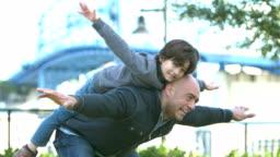 Hispanic boy sitting on father's back, flying