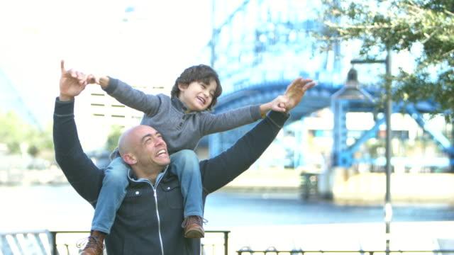 vidéos et rushes de garçon hispanique s'asseyant sur les épaules du père ayant l'amusement - les bras écartés