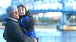 Hispanic boy with father on city waterfront in winter