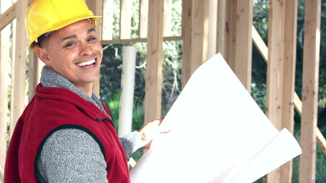 Hispanic building contractor at job site with plans