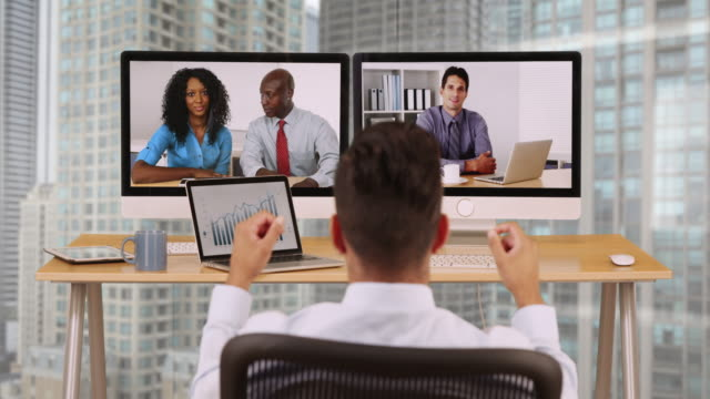 vídeos de stock, filmes e b-roll de hispanic business man in high rise corporate office having internet video conference with diverse group of coworkers - envolvimento dos funcionários