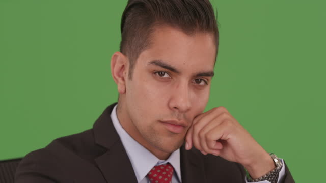 vídeos de stock, filmes e b-roll de hispanic business man looking at camera wearing suit and tie on green screen - neckwear