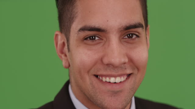 vídeos de stock, filmes e b-roll de hispanic business man smiling and wearing suit and tie on green screen - neckwear