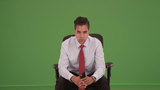 vídeos de stock, filmes e b-roll de hispanic business professional sitting looking at camera on green screen - neckwear