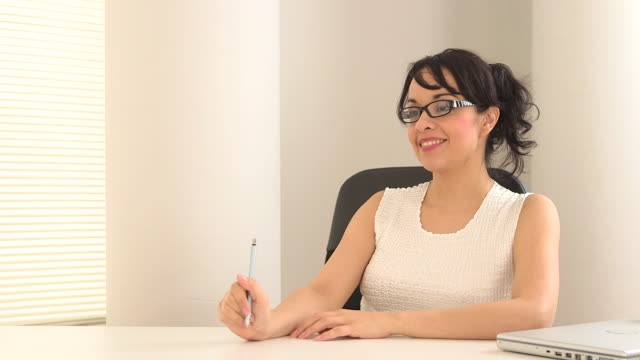 Hispanic business woman sitting at a desk talking