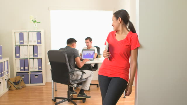 hispanic business woman smiling with colleagues in background - dreiviertelansicht stock-videos und b-roll-filmmaterial