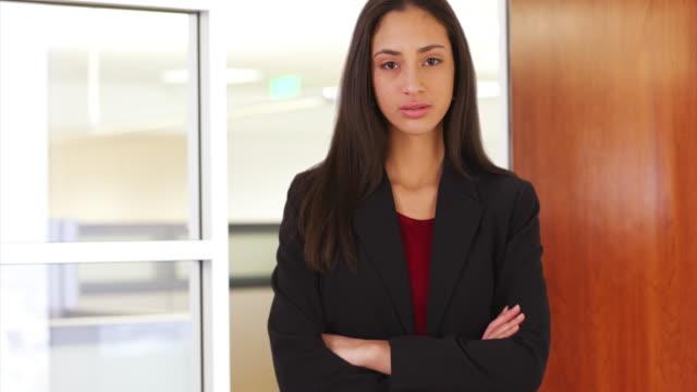 vídeos y material grabado en eventos de stock de a hispanic businesswoman poses for a portrait in the doorway to an office - vestimenta de negocios formal