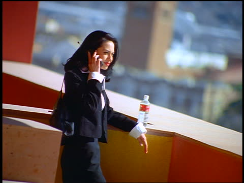 canted hispanic businesswoman talking on cellular phone outdoors / water bottle next to her - weibliche angestellte stock-videos und b-roll-filmmaterial