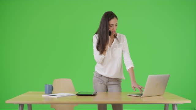 a hispanic businesswoman talks on her mobile phone on green screen - digital spegelreflexkamera bildbanksvideor och videomaterial från bakom kulisserna