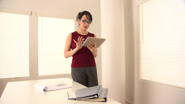 Hispanic businesswoman using tablet in office