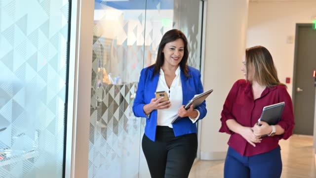 vídeos de stock, filmes e b-roll de empresárias hispânicas andando juntas no escritório moderno - 40 49 anos
