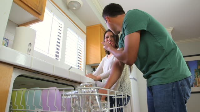 hispanic couple doing dishes - dreiviertelansicht stock-videos und b-roll-filmmaterial