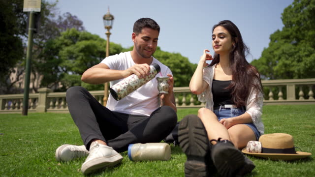 hispanic couple enjoying yerba mate while relaxing on grass - falling in love stock videos & royalty-free footage