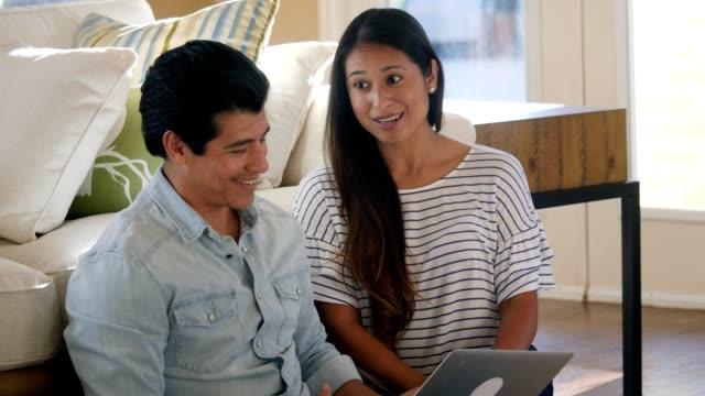 vídeos y material grabado en eventos de stock de pareja hispana utiliza ordenador portátil en casa - usar el ordenador