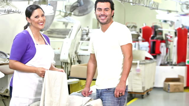 hispanic couple working in dry cleaner store - launderette stock videos and b-roll footage