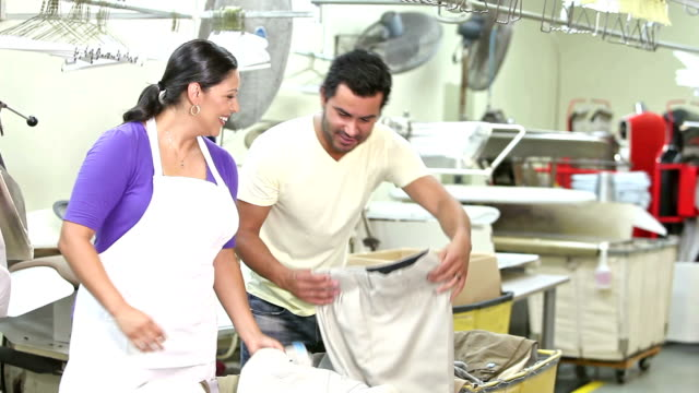 hispanic couple working in dry cleaner store - minority groups stock videos and b-roll footage