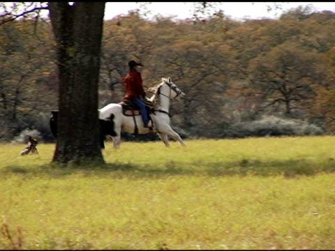 Hispanic Cowboys reiten White Horse auf Texas Ranch