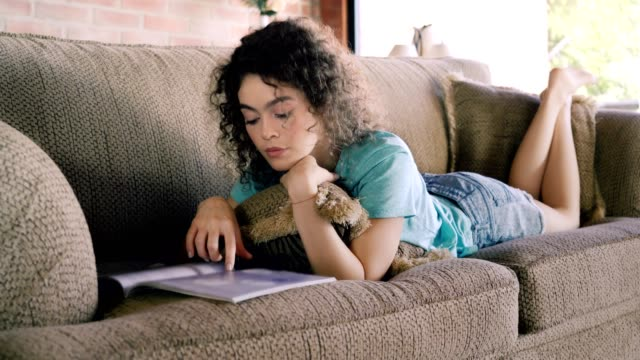 hispanic curly hair young woman reading a magazine while relaxing on a sofa - magazine publication stock videos & royalty-free footage