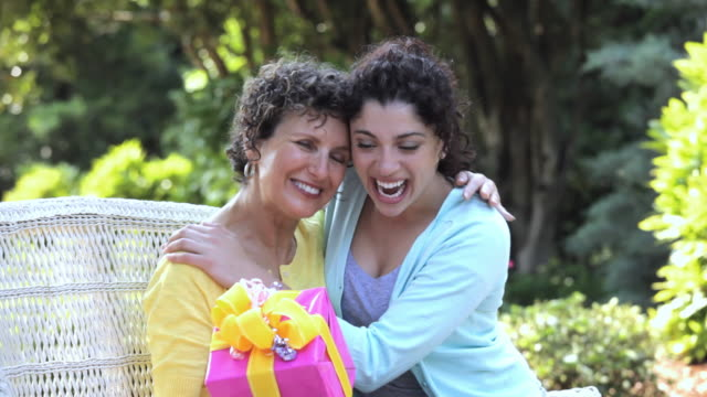 pan hispanic daughter greeting mother with present, richmond, virginia, united states - mother's day stock videos & royalty-free footage