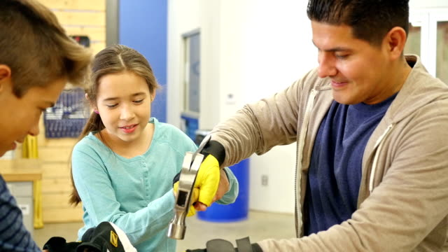 Hispanic elementary age girl hammers nail in board at community woodworking workshop