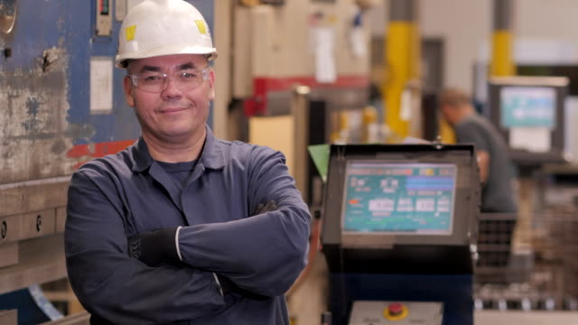 hispanic equipment operator posing in metal fabrication facility - metal blend stock videos and b-roll footage
