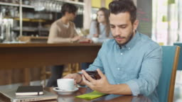 Hispanic Ethnicity Young Man using Mobile Phone at Cozy Coffee Shop.