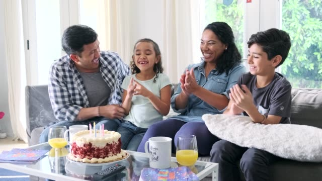 Hispanic family celebrating a birthday with cake