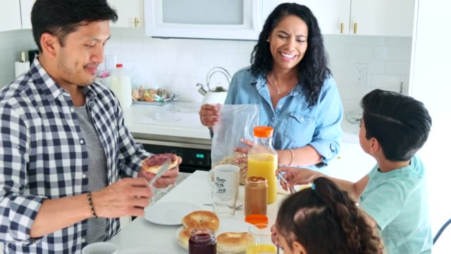 Hispanic family eating breakfast in the kitchen