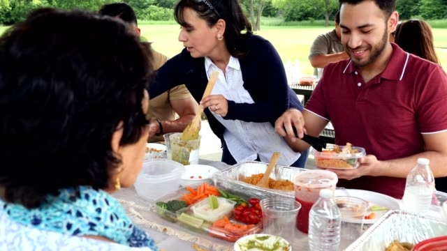hispanic family enjoy a meal together during a family reunion - large family stock videos & royalty-free footage
